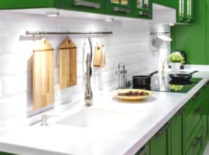 clean quartz countertop with green cabinets